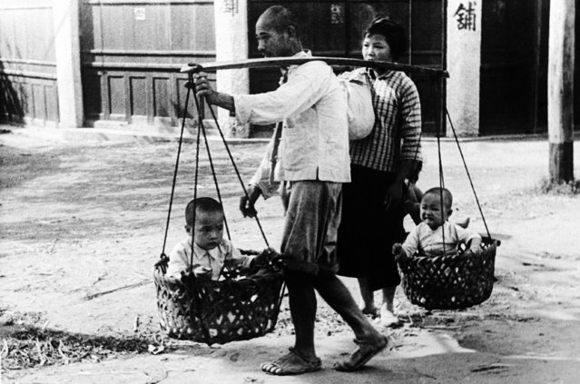 As usual, the poorest people in China are suffering the most in Japan's ruthless campaign to demoralize the non-combatants. A war refugee family on the move from Shanghai, on September 28, 1937. The babes are balanced on the contraption on father's shoulder, while mother carries all that remains of the family possessions. (Photo by AP Photo)