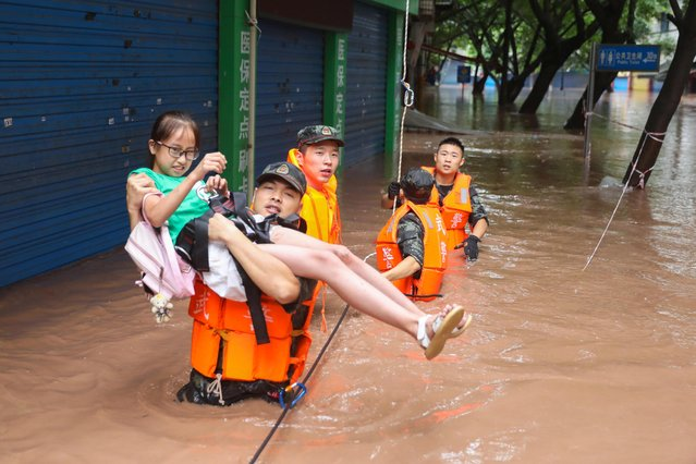 A paramilitary police officer evacuates a resident while he wades through floodwaters following a heavy rainfall in Wanzhou of Chongqing, China on July 16, 2020. (Photo by China Daily via Reuters)
