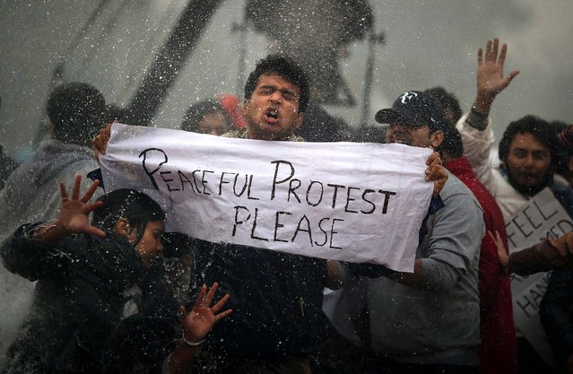 Protesters react as Indian police officers use a water cannon to disperse them near the India Gate as they protest against the gang rape and brutal beating of a 23-year-old student on a bus last week, in New Delhi, India, on December 23, 2012. The attack last Sunday has sparked days of protests across the country. Thousands gathered to protest against current rape laws and government handling of recent rape cases all over India. (Photo by Saurabh Das/Associated Press)