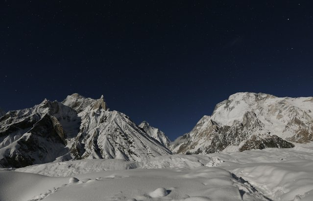 The world's second largest mountain, K2 (seen in the distance), and Broad Peak (R), are illuminated by the moon at Concordia, the confluence of the Baltoro and Godwin-Austen glaciers, in the Karakoram mountain range in Pakistan September 7, 2014. (Photo by Wolfgang Rattay/Reuters)