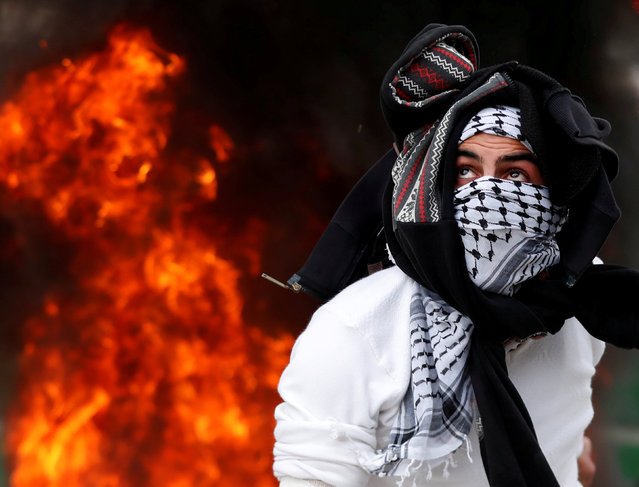 A Palestinian protester throws a stone at Israeli forces during protest against U.S. President Donald Trump's decision to recognize Jerusalem as the capital of Israel, near Qalandia checkpoint near the West Bank city of Ramallah, December 20, 2017. (Photo by Goran Tomasevic/Reuters)