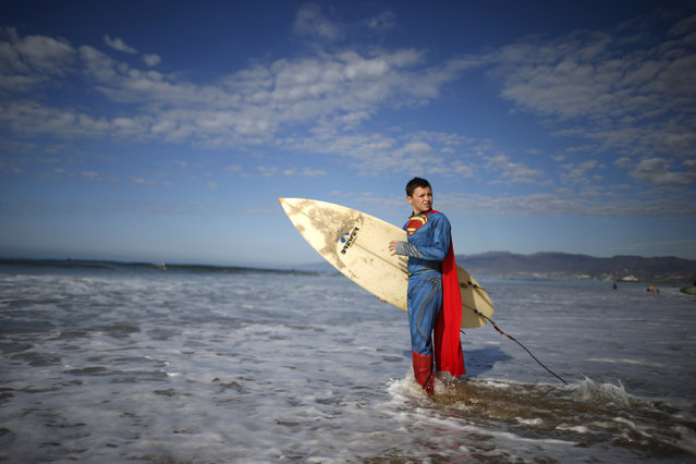 Catello Dannunzio, 12, prepares to compete as Superman during the 7th annual ZJ Boarding House Haunted Heats Halloween surf contest. (Photo by Lucy Nicholson/Reuters)