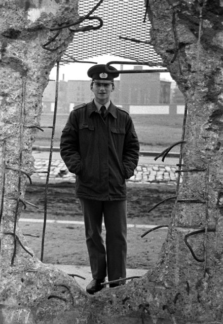 An East German border soldier looks through a large hole into the Berlin Wall after the opening of the East German border was announced, February 8, 1990. (Photo by Reuters)