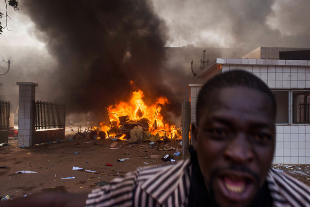 A car burns outside the parliament building in Burkina Faso as people protest  against their longtime president  Blaise Compaore who is  seeking another term in Ouagadougou, Burkina Faso, Thursday, October 30, 2014. Protesters stormed Burkina Faso's parliament Thursday, dragging furniture and computers onto the street and setting the main chamber ablaze, in the most significant challenge to the president's rule during his 27 years in power. (Photo by Theo Renaut/AP Photo)