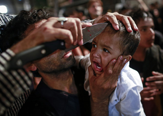 A Shi'ite Muslim has his child gashed with a knife during a Muharram procession ahead of Ashura in Mumbai November 3, 2014. (Photo by Danish Siddiqui/Reuters)