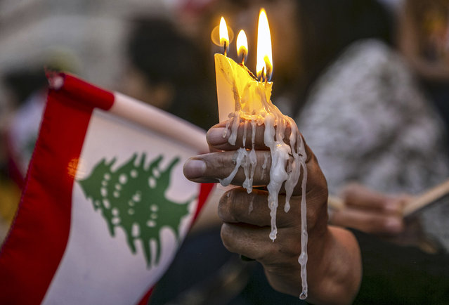 Tunisians light a candle during a demonstration in support of Lebanese people following the explosion in the port of Beirut, on August 06, 2020 in Tunis, Tunisia. (Photo by Yassine Gaidi/Anadolu Agency via Getty Images)
