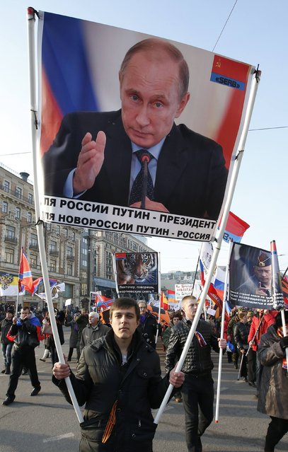 "A man carries a portrait of Russia's President Vladimir Putin as he attends a demonstration on National Unity Day in Moscow November 4, 2014. The sign reads: ""I want in to the USSR"". (Photo by Sergei Karpukhin/Reuters)"