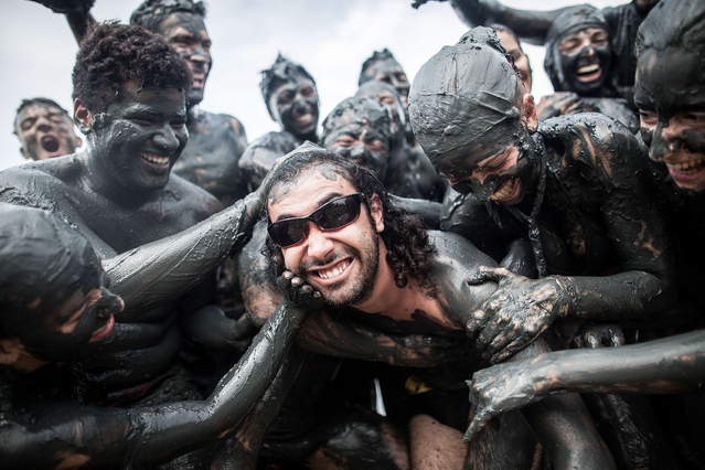 Revelers participate in the traditional Bloco da Lama (Mud block) carnival in Parati, Rio de Janeiro State, Brazil, on February 9, 2013. The event, which was begun by two men in a playful manner in 1986, has now become a traditional carnival in which participants disguised as primitives with rags, lianas or skulls and bones, dive in the mud. (Photo by Victor Moriyama/AFP Photo)