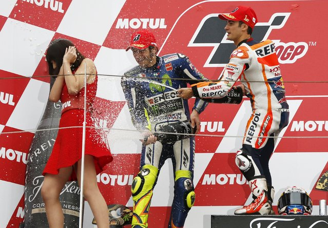 Honda MotoGP rider Dani Pedrosa (R) of Spain sprays champagne on an attendant next to Yamaha MotoGP rider Valentino Rossi (C) of Italy after winning the Japanese Grand Prix at the Twin Ring Motegi circuit in Motegi, north of Tokyo, Japan, October 11, 2015. Rossi placed second. (Photo by Issei Kato/Reuters)