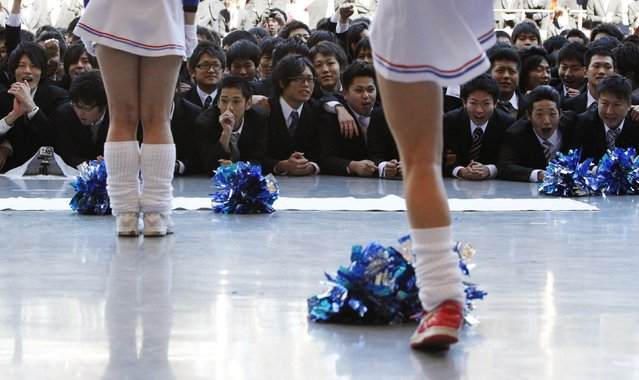 Japanese college students watch cheerleaders perform at a job-hunting rally in Tokyo February 13, 2013. About 1,500 students from vocational schools attended the rally to boost their morale ahead of their job hunt. (Photo by Yuya Shino/Reuters)