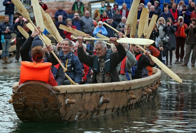 Crew in Britain's first ever full-size reconstructed sea-going Bronze Age boat, raise their paddles out as it makes its maiden voyage on March 6, 2013 in Falmouth, England. With a crew of of 18, equipped with Bronze-Age-style wooden paddles, the 15 metre long experimental vessel – a replica of the sort of craft used for long-distance trade between Britain and the continent 4000 years ago – will be used to test prehistoric seafaring methods in a project in collaboration with the University of Exeter and the Falmouth-based National Maritime Museum Cornwall. (Photo by Matt Cardy)