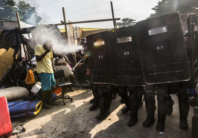 Riot police use pepper gas against residents of the Telerj slum as they attempt to repossess the land in Rio de Janeiro, in this April 11, 2014 file picture. I was shooting the clear-out by the police of a building which belonged to a giant telecommunications company and had been taken over by homeless people a week earlier. It was my third day there as I was doing a photo essay on the occupation and I was more interested in the aesthetics of the shacks and how people managed to build a home. (Photo and caption by Ana Carolina Fernandez/Reuters)