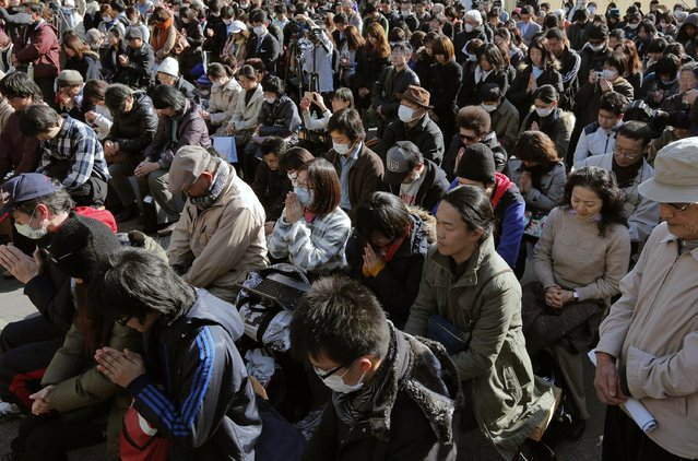 People observe a moment of silence for the victims of the March 11, 2011 earthquake and tsunami during an event at a park in Tokyo, at 2:46 p.m. on Monday. (Photo by Itsuo Inouye/AP Photo)