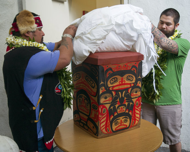 Tlingit Tribe members from Klawock, Alaska Jonathan Rowan, left, and Lawrence Armour unveil a carved Alaskan storage box at the Honolulu Museum of Arts, Thursday, October 22, 2015, in Honolulu. The box was a thank you gift for the return of their totem pole. (Photo by Marco Garcia/AP Photo)