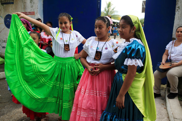 Girls watch a procession during festivities in honour of St. Michael the Archangel in San Miguel Tepezontes, El Salvador September 28, 2016. (Photo by Jose Cabezas/Reuters)