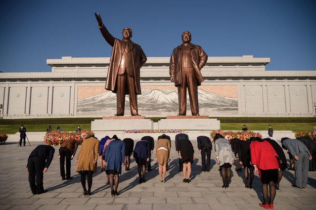 People bow before the statues of late North Korean leaders Kim Il Sung and Kim Jong Il at Mansu hill as the country marks the 75th founding anniversary of the Workers' Party of Korea, in Pyongyang on October 10, 2020. (Photo by KIM Won Jin/AFP Photo)