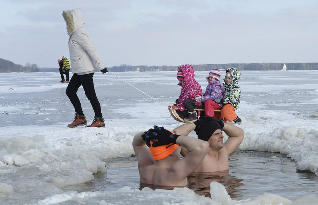 Children enjoy a sledge ride past ice swimming fans at the Zalew Zegrzynski lake in Nieporet, Poland, Sunday, February 25, 2018. A cold wave hit Poland with the temperature minus 8 degree Celsius (17.6 Fahrenheit) during the day and dropping to minus 16 degree Celsius (3.2 Fahrenheit) in the night in central Poland. (Photo by Alik Keplicz/AP Photo)