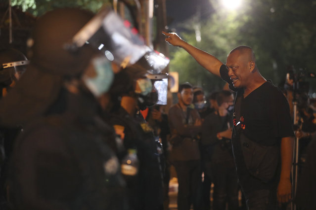 A pro-democracy protester shouts at Thai policemen during a demonstration in Bangkok, Thailand, Thursday, October 15, 2020. Thai police dispersed a group of protesters holding an overnight rally outside the prime minister's office. (Photo by Rapeephat Sitichailapa/AP Photo)