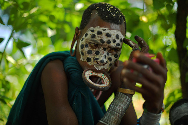 """A woman from the Suri tribe wearing a lip plate paints her face in Ethiopia's southern Omo Valley region near Kibbish on September 25, 2016. The Suri are a pastoralist Nilotic ethnic group in Ethiopia. The construction of the Gibe III dam, the third largest hydroelectric plant in Africa, and large areas of very """"thirsty"""" cotton and sugar plantations and factories along the Omo river are impacting heavily on the lives of tribes living in the Omo Valley who depend on the river for their survival and way of life. Human rights groups fear for the future of the tribes if they are forced to scatter, give up traditional ways through loss of land or ability to keep cattle as globalisation and development increases. (Photo by Carl De Souza/AFP Photo)"""