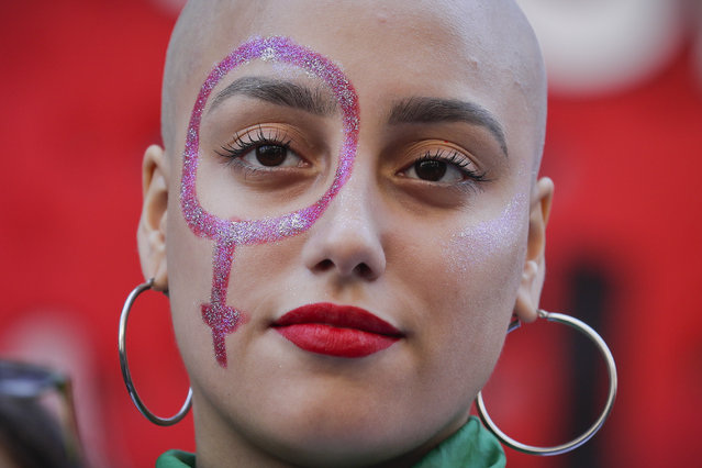 A pro-abortion activist with a Venus symbol painted on her face listens to a speech outside of Congress after the presentation of an abortion bill in Buenos Aires, Argentina, Tuesday, March 6, 2018. Under heavy pressure by women's groups that have taken to the streets in large numbers in recent years, over 70 legislators presented an abortion bill that will be first be discussed in several committees of the lower chamber. (Photo by Victor R. Caivano/AP Photo)