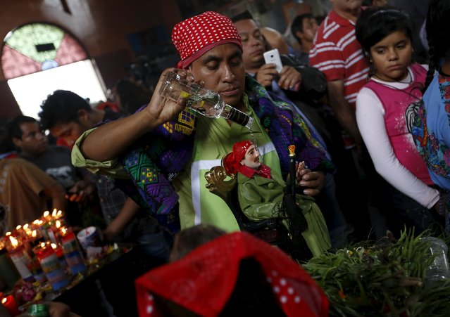 A man pours aguardiente over an effigy of San Simon in a church in his honor in Chimaltenango, around 62 km (39 miles), from Guatemala City, October 28, 2015. People in Guatemala revere San Simon, also known by his Mayan name Maximon o Ry Laj Man, on October 28 annually. For some devotees, San Simon is synonymous with prosperity and happiness, while others associate him with witchcraft, paganism and a protector for drunkards. Since the 19th century, devotees have offered money, liquor or tobacco in exchange for his blessings. (Photo by Jorge Dan Lopez/Reuters)