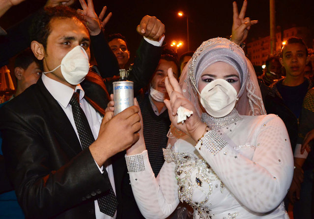 Revolutionary activist Mohammed Magdy and his bride, wear masks against tear gas and jointly hold a used tear gas container, celebrating their wedding in Revolution Square, the center of weeks of anti-government clashes, in the Nile Delta city of Mansoura, Egypt, on March 4, 2013. Protesters in Mansoura, and other Egyptian cities have been calling for civil disobedience campaigns, or work stoppages, to bring down President Mohammed Morsi who they accuse along with the Muslim Brotherhood of trying to monopolize power and of reneging on promises of reform. (Photo by AP Photo /The Atlantic)