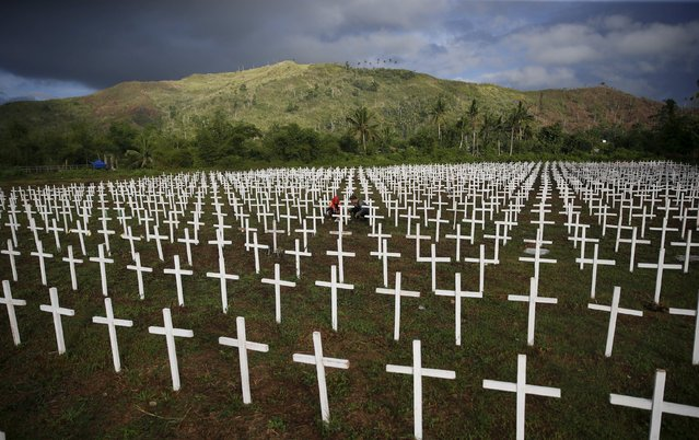 A couple visiting the graves of their four children is seen among thousands of crosses at a mass grave for Typhoon Haiyan victims on All Saints Day in Tacloban city in central Philippines November 1, 2015, and ahead of the second anniversary of the devastating typhoon that killed more than 6,000 people in central Philippines. (Photo by Erik De Castro/Reuters)