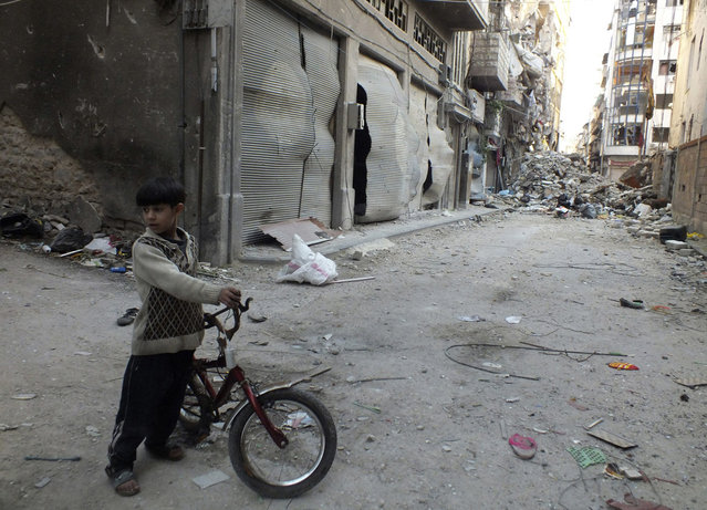 A boy holds a bicycle near debris and damaged buildings in Homs, on March 25, 2013. (Photo by Yazan Homsy/Reuters /The Atlantic)