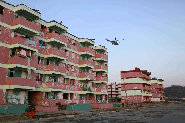 An army helicopter flies over damaged buildings after the passage of Hurricane Matthew in Baracoa, Cuba October 7, 2016. (Photo by Alexandre Meneghini/Reuters)