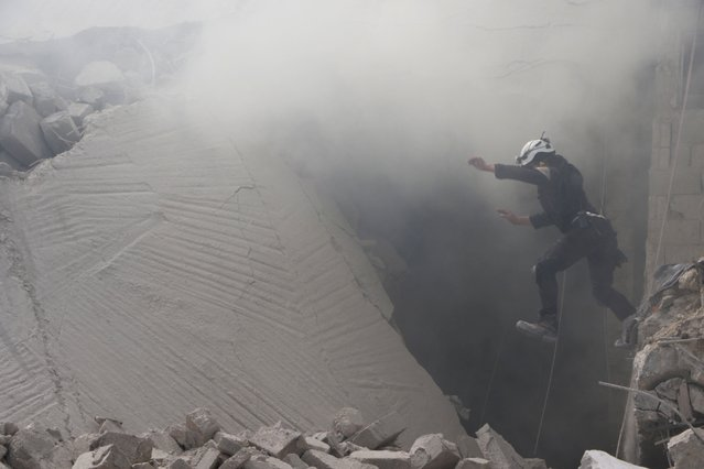 A civil defense member carries out a search and rescue operation over the wreckage of collapsed buildings after the airstrike belonging to Syrian army targeted at opposition controlled in Bab al-Nairab district in Aleppo, Syria on August 27, 2016. It is reported that many people killed and wounded after the airstrike. (Photo by Ibrahim Ebu Leys/Anadolu Agency/Getty Images)