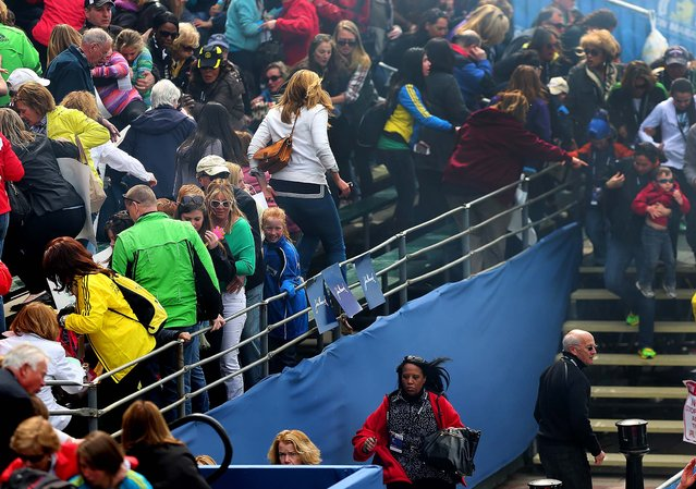 Spectators rush to leave the stands after an explosion at the Boston Marathon, April 15, 2013. (Photo by David L. Ryan/The Boston Globe)
