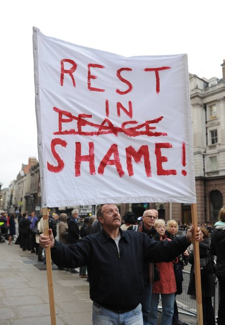 Phil Williams from Chester holds a banner outside the Courts of Justice in the Strand prior to the funeral service of Baroness Thatcher at St Paul's Cathedral, central London, on April 17, 2013. (Photo by Joe Giddens/PA Wire)