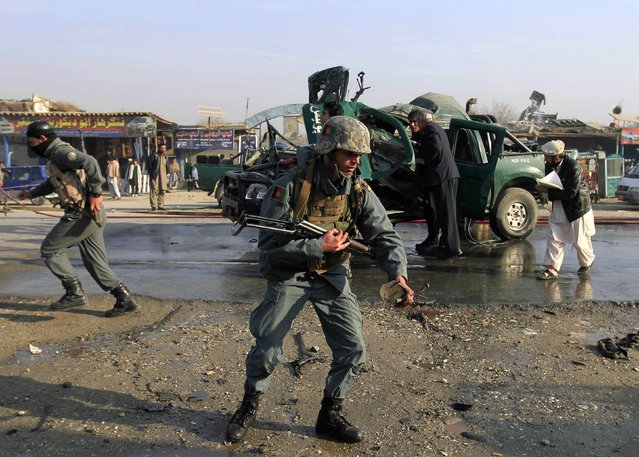 Afghan policemen inspect the site of a bomb explosion in Jalalabad, December 17, 2014. A magnetic bomb attached to a police car exploded in eastern Afghanistan, killed two policemen and wounded five other, the provincial spokesman Ahmadzia Abdulzai said. (Photo by Reuters/Parwiz)