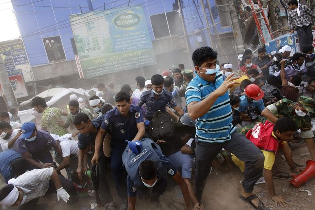 Rescue workers, army personnel, police and members of media run after they heard someone shouting that a building next to Rana Plaza is collapsing during a rescue operation in Savar, 19 miles outside Dhaka April 26, 2013. The search for survivors from Bangladesh's worst industrial accident stretched into a third day on Friday, with the death toll rising to 273 after the collapse of Rana Plaza. (Photo by Andrew Biraj/Reuters)