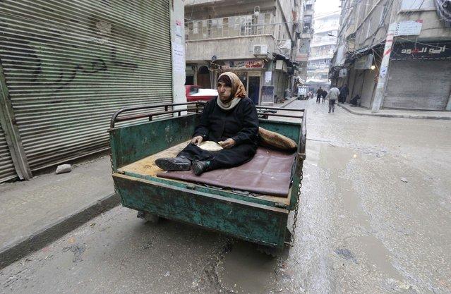 A woman eats bread as she sits on a pick-up truck in al-Shaar neighbourhood of Aleppo December 28, 2014. (Photo by Abdalrhman Ismail/Reuters)