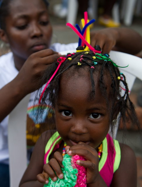 A girl gets an Afro-Colombian hairstyle during the 9th contest of Afro-hairdressers, in Cali, Valle del Cauca departament, Colombia, on May 12, 2013. The Afro hairstyles have their origins in the time of slavery, when women sat to comb their children hair after work. (Photo by Luis Robayo/AFP Photo)