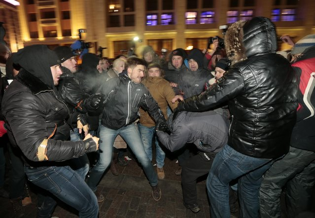 Supporters and opponents of Russian opposition activist and anti-corruption crusader Alexei Navalny clash during unsanctioned protest in Manezhnaya Square in Moscow, Russia, Tuesday, December 30, 2014. The unsanctioned protest came hours after Alexei Navalny was found guilty of fraud and given a suspended sentence. Navalny, who has been under house arrest since February. (Photo by Ivan Sekretarev/AP Photo)
