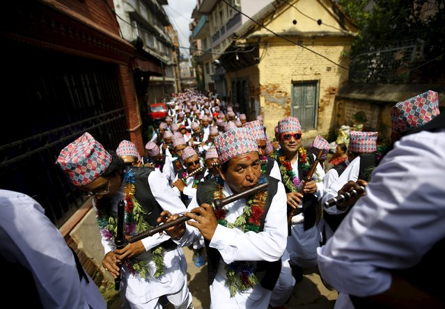 Devotees in traditional attire play flutes as they take part in a parade commemorating the Neku Jatra-Mataya festival, the Festival of Lights, in Lalitpur, Nepal August 31, 2015. Devotees celebrate the Buddhist festival which marks the victory of Sakyamuni Buddha over Mara, by praying for the souls of departed family members and holding parades throughout the city. (Photo by Navesh Chitrakar/Reuters)