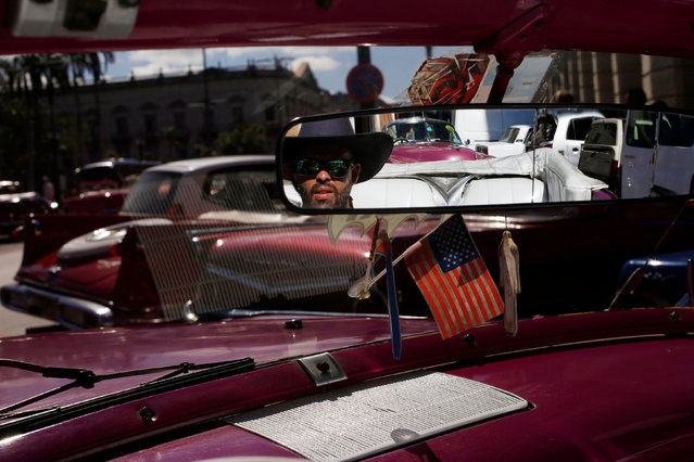 A driver of a vintage car used take tourists for a ride, waits for costumers with a U.S. flag on its windshield in Havana, Cuba, November 8, 2017. (Photo by Reuters/Stringer)