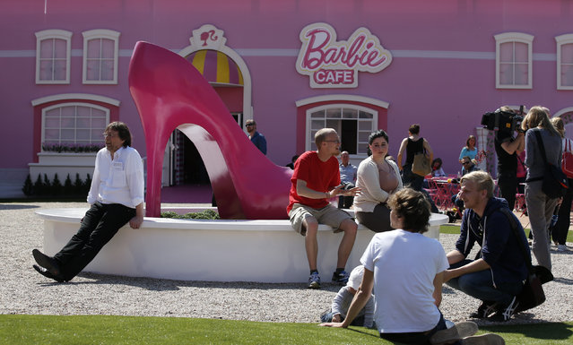 """People relax outside a """"Barbie Dreamhouse"""" of Mattel's Barbie dolls in Berlin, May 16, 2013. (Photo by Fabrizio Bensch/Reuters)"""