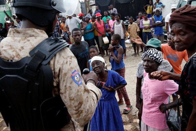 A woman talks to a police officer outside a distribution of food and relief kits after Hurricane Matthew hit Jeremie, Haiti, October 19, 2016. (Photo by Carlos Garcia Rawlins/Reuters)