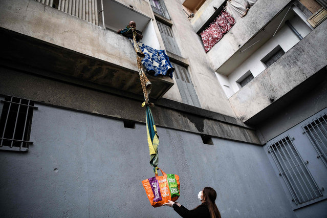 A resident of the White House estate, a private condominium of 226 mostly unsanitary dwellings, collects food offered by neighbours from his balcony, using a rope made with blankets, on March 31, 2020, in Marseille, southern France, on the fifteenth day of a lockdown aimed at curbing the spread of the COVID-19 (novel coronavirus). (Photo by Anne-Christine Poujoulat/AFP Photo)