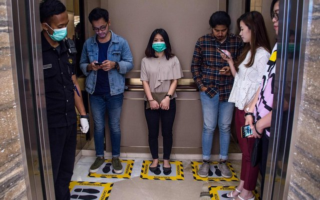 People stand on designated areas to ensure social distancing inside an elevator at a shopping mall in Surabaya on March 19, 2020, amid concerns of the COVID-19 coronavirus outbreak. (Photo by Juni Kriswanto/AFP Photo)
