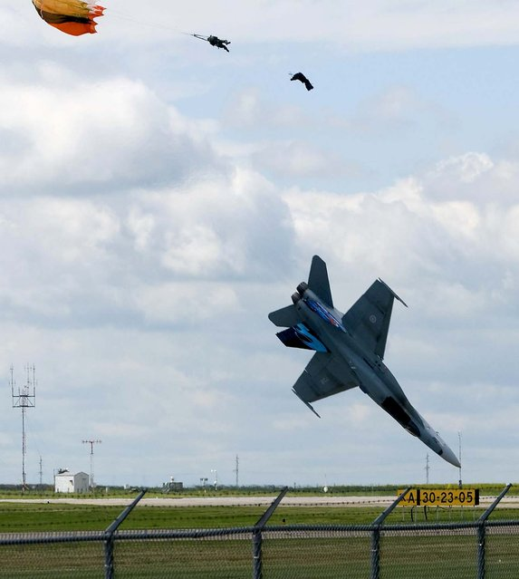 Pilot Capt. Brian Bews parachutes to safety as his CF-18 fighter jet plummets to the ground during a practice flight for a weekend airshow at the Lethbridge County Airport in Alberta, Canada. (Photo by Ian Martens/Lethbridge Herald/The Canadian Press/Associated Press)
