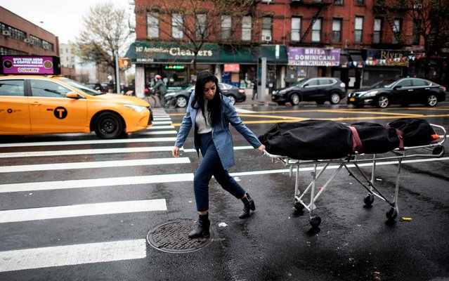 Alisha Narvaez Manager at International Funeral & Cremation Services transports a body to the funeral home on April 24, 2020 in the Harlem neighborhood of New York City. For many families already in distress, finding a funeral home in New York that will accept the body of a loved one is a headache; in Harlem, International Funeral home tries not to turn anyone away, even if it means being under stress. (Photo by Johannes Eisele/AFP Photo)