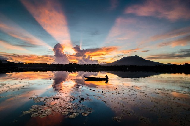 """Rays of Sunrise"". Amazing moments when rays of sun appear at sunrise its only last for a few seconds, still water, reflection and a fisherman passing thru. Location: Sampaloc lake, San Pablo City, Laguna, Philippine. (Photo and caption by Danilo Dungo/National Geographic Traveler Photo Contest)"
