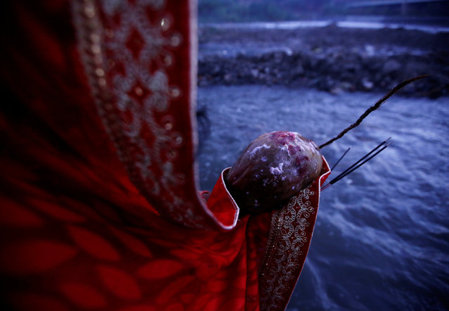 """A devotee holding offering and incense in her hands offers prayers to the rising sun during the """"Chhat"""" festival at Bagmati River in Kathmandu, Nepal November 7, 2016. (Photo by Navesh Chitrakar/Reuters)"""