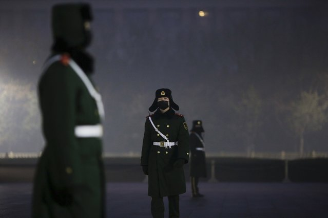 "Paramilitary policemen wear masks on a cold morning as people gather for a flag-raising ceremony amid heavy smog at the Tiananmen Square, after the city issued its first ever ""red alert"" for air pollution, in Beijing December 9, 2015. (Photo by Damir Sagolj/Reuters)"