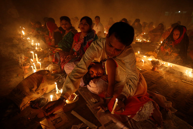 A girl sleeps on her fatherÕs lap as to observe Rakher Upabash, in Narayangonj near Dhaka, Bangladesh, November 8, 2016. (Photo by Mohammad Ponir Hossain/Reuters)