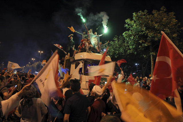 Supporters of Turkey's President and ruling Justice and Development Party, or AKP, leader Recep Tayyip Erdogan celebrate atop a truck outside the party headquarters in Istanbul, Sunday, June 24, 2018. Unofficial results from Turkey's presidential election show incumbent Recep Tayyip Erdogan with a commanding lead. (Photo by AP Photo/Stringer)